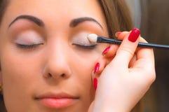 Het toepassen van oogschaduw op ooglid Stock Afbeeldingen