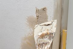 Het toepassen van stopverf op de muur in een nieuwe flat Vernieuwing en het schilderen van muren thuis stock afbeeldingen