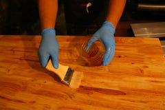 Het toepassen van vernis op een houten oppervlakte met een borstel Stock Afbeelding