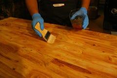 Het toepassen van vernis op een houten oppervlakte met een borstel Stock Foto