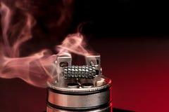 Het toepassen van vloeistof met nicotine in de rollen op RDA Stock Afbeelding