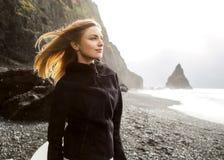 Het toeristenmeisje bevindt zich op het strand bij zonsondergang royalty-vrije stock foto's