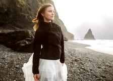 Het toeristenmeisje bevindt zich op het strand bij zonsondergang royalty-vrije stock fotografie