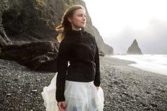 Het toeristenmeisje bevindt zich op het strand bij zonsondergang stock afbeeldingen