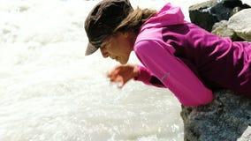 Het toeristenmeisje drinkt water met handen van dichte omhooggaand van de bergrivier stock footage