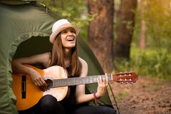 Het toeristenmeisje in hoed zit in tent en speelgitaarconcept Toerismerust op aard royalty-vrije stock fotografie