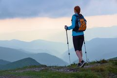 Het toeristenmeisje met achterzak en volgende stokken blijft op het gazon Mooie hemel De daling van zonstralen neer op de bergen Royalty-vrije Stock Foto