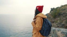 Het toeristenmeisje met een rugzak die zich op de rand van een klip bevinden en geniet van een mooie mening stock footage