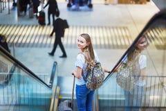 Het toeristenmeisje met rugzak en draagt bagage in internationale luchthaven, op roltrap Stock Foto's