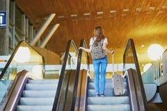 Het toeristenmeisje met rugzak en draagt bagage in internationale luchthaven, op roltrap stock afbeelding