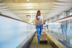 Het toeristenmeisje met rugzak en draagt bagage in internationale luchthaven, op travelator Stock Foto