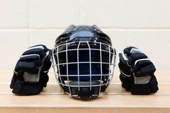Het toestel van het jong geitje` s hockey op de bank: zwarte hockeyhelm en handschoenen royalty-vrije stock afbeelding
