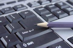 Het toetsenbord en het potlood stock foto