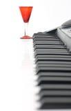 Het toetsenbord van de piano en rood glas Royalty-vrije Stock Fotografie