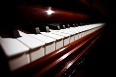 Het toetsenbord van de piano onder zachte verlichting Stock Afbeeldingen
