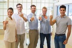 Het toevallige commerciële team roosteren met champagne aan camera Stock Foto's