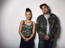 Het toevallige jonge hipsterpaar stellen samen tegen grijze achtergrond royalty-vrije stock afbeelding