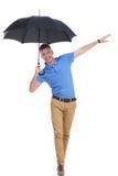 Het toevallige jonge mens in evenwicht brengen met paraplu Royalty-vrije Stock Afbeeldingen