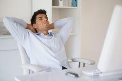 Het toevallige zakenman ontspannen bij bureau die terug leunen stock afbeelding