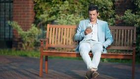 Het toevallige zakenman texting op telefoon op parkbank op een zonnige dag stock video