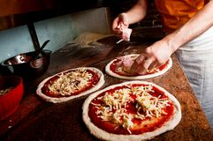 Het toevoegen van bacon aan pizza Stock Foto