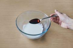 Het toevoegen van de ingrediënten van bessenalcoholische drank door een lepel in de kom royalty-vrije stock foto
