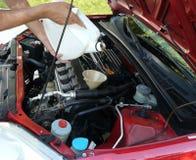 Het toevoegen van de Olie van de Motor aan Auto stock afbeelding