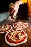 Het toevoegen van extra eerste persing aan Pizza Royalty-vrije Stock Afbeelding