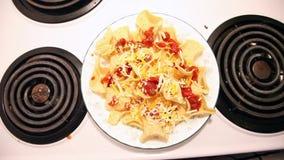 Het toevoegen van kaas aan plaat van nachos stock footage