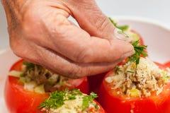 Het toevoegen van koriander aan ruwe gevulde tomaten Royalty-vrije Stock Afbeelding