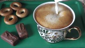 Het toevoegen van melk aan vers gebrouwen koffie stock videobeelden