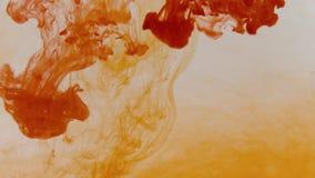 Het toevoegen van rode kleurstof in het oranje water stock video