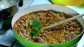 Het toevoegen van sommige groene kruiden op de sojamaaltijd in de pan stock video