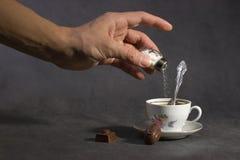Het toevoegen van vergift aan koffie Stock Afbeeldingen