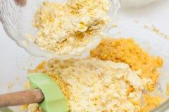 Het toevoegen van verscheurde graanpitten om suikermaïsbrood voor te bereiden Royalty-vrije Stock Afbeelding