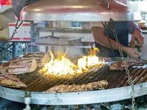 Het toevoegen van zout op geroosterd vlees in grote koperslager Stock Foto