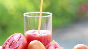 Het tomatesap wordt gegoten in een glas stock video