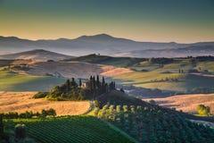 Het toneellandschap van Toscanië met rollende heuvels en valleien bij zonsopgang stock afbeeldingen