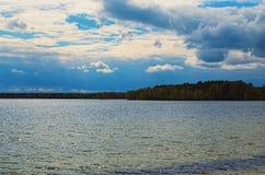Het toneelmeerlandschap in de bosstralen van de zon wordt weerspiegeld in het blauwe water Pisochneozero Stock Afbeeldingen