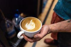 Het tonen van een lattekoffie royalty-vrije stock afbeelding