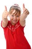 Het tonen van het meisje beduimelt omhoog gebaar dat op wit wordt geïsoleerdg Stock Foto's