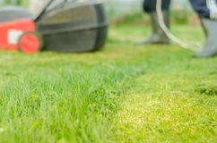Het Tonsuredgazon en de rode grasmaaimachine/de grasmaaimachine worden schoongemaakt van een gras Selectieve nadruk stock afbeeldingen