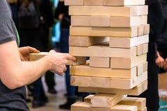 Het torenblok, mens neemt een houten deel van houten toren Planning, r royalty-vrije stock foto's