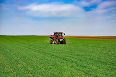 Het tractorwerk aangaande het gebied Het toepassen van meststof in de lente stock foto