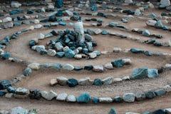 Het traditionele die labyrint van het natuursteenlabyrint maakte voor overpeinzing en verering, met rotsen in schaduwen van blauw stock afbeeldingen