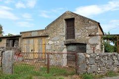 Het traditionele die steenhuis door eigenaars met deuren en vensters wordt verlaten sloot met geïmproviseerde die deuren van hout royalty-vrije stock foto's