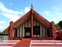 Het traditionele houten huis van het Maorivoedsel gesneden met decoratie Nieuw Zeeland stock afbeelding