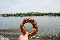 Het traditionele Turkse ongezuurde broodje genoemd wordt Simit gehouden door een mens in de hand op de achtergrond van Bosphorus  stock afbeeldingen