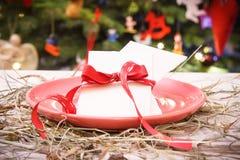 Het traditionele wafeltje van de Kerstmisvooravond op lijst met hooi en Kerstmisboom met lichten en decoratie, het concept van de stock afbeeldingen