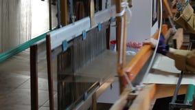 Het traditionele weefgetouw van de zijdestof De oude wevende machine van de zijdestof Stof van de vrouwen de wevende zijde op wee stock footage